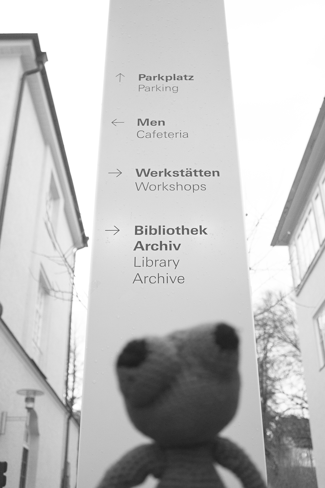 teddy bear looking at sign with directions to different rooms in the inner yard of the university of design in Schwäbisch Gmünd