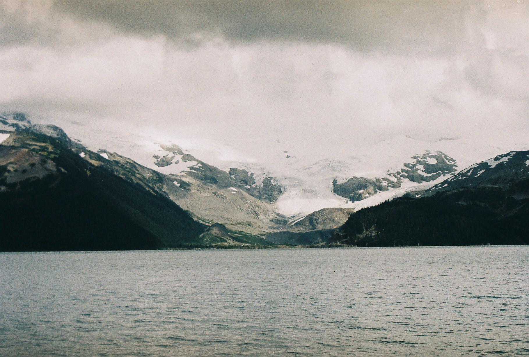 Kanadischer See vor Berglandschaft mit Schnee auf den Gipfeln