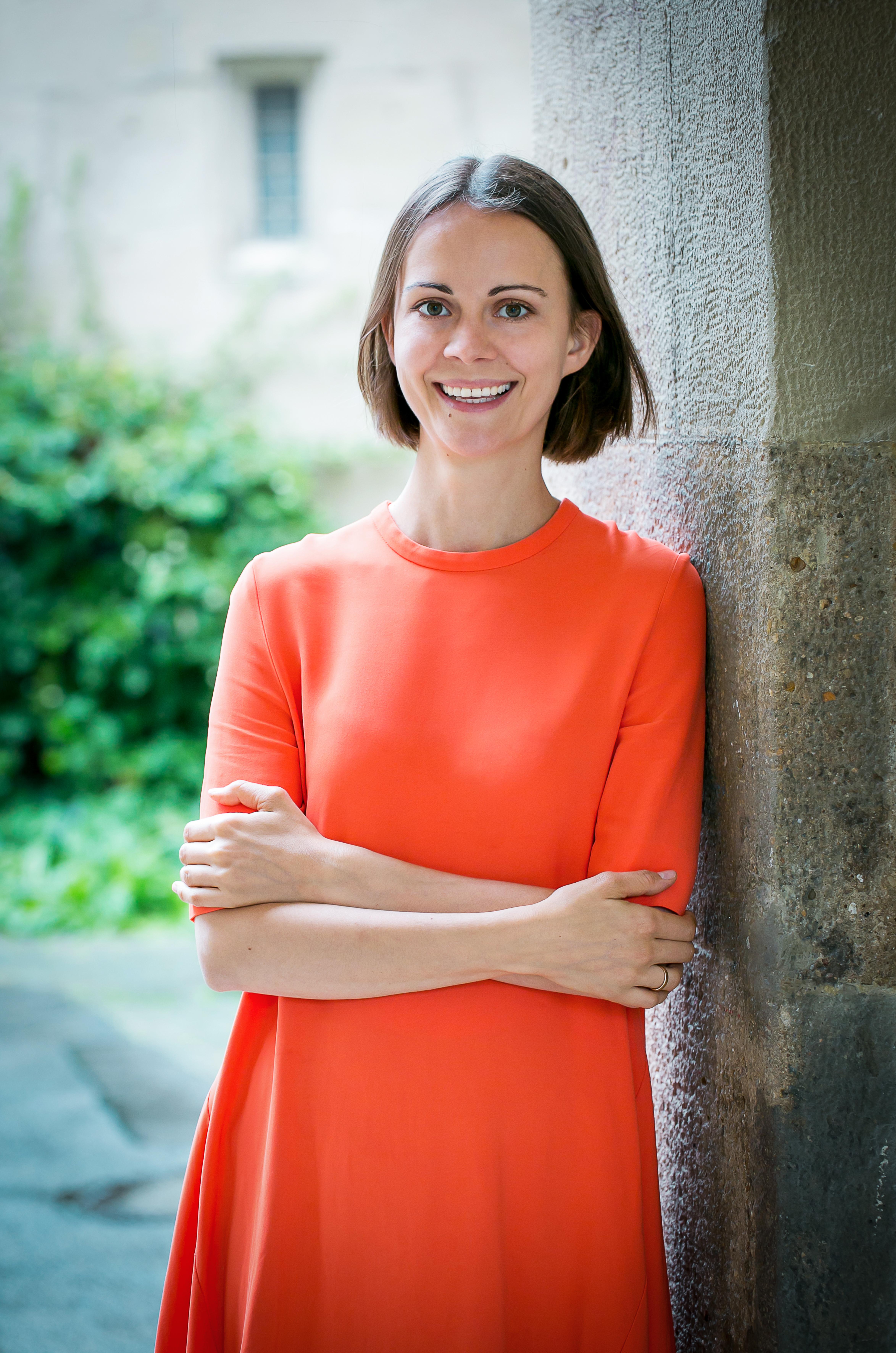 lächelnde, braunhaarige Frau in orangenem Kleid angelehnt an Mauer vor Grünstreifen