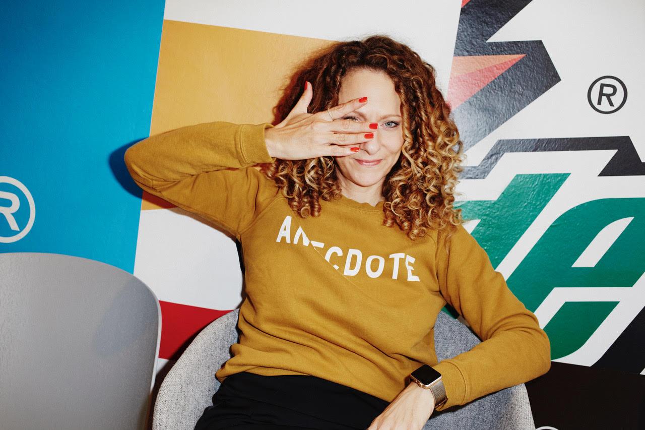 Junge braun gelockte Frau mit gelben Pullover vor bunter Grafitti wand