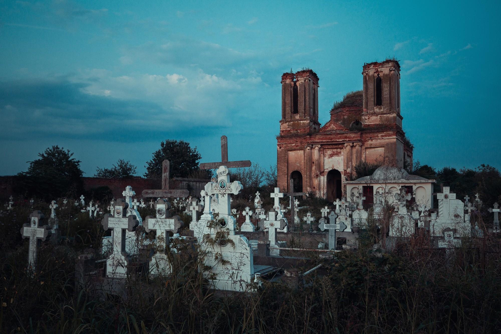 Fotografie einer bemoosten Kirchen-Ruine, die hinter weißen Grabsteinen steht.