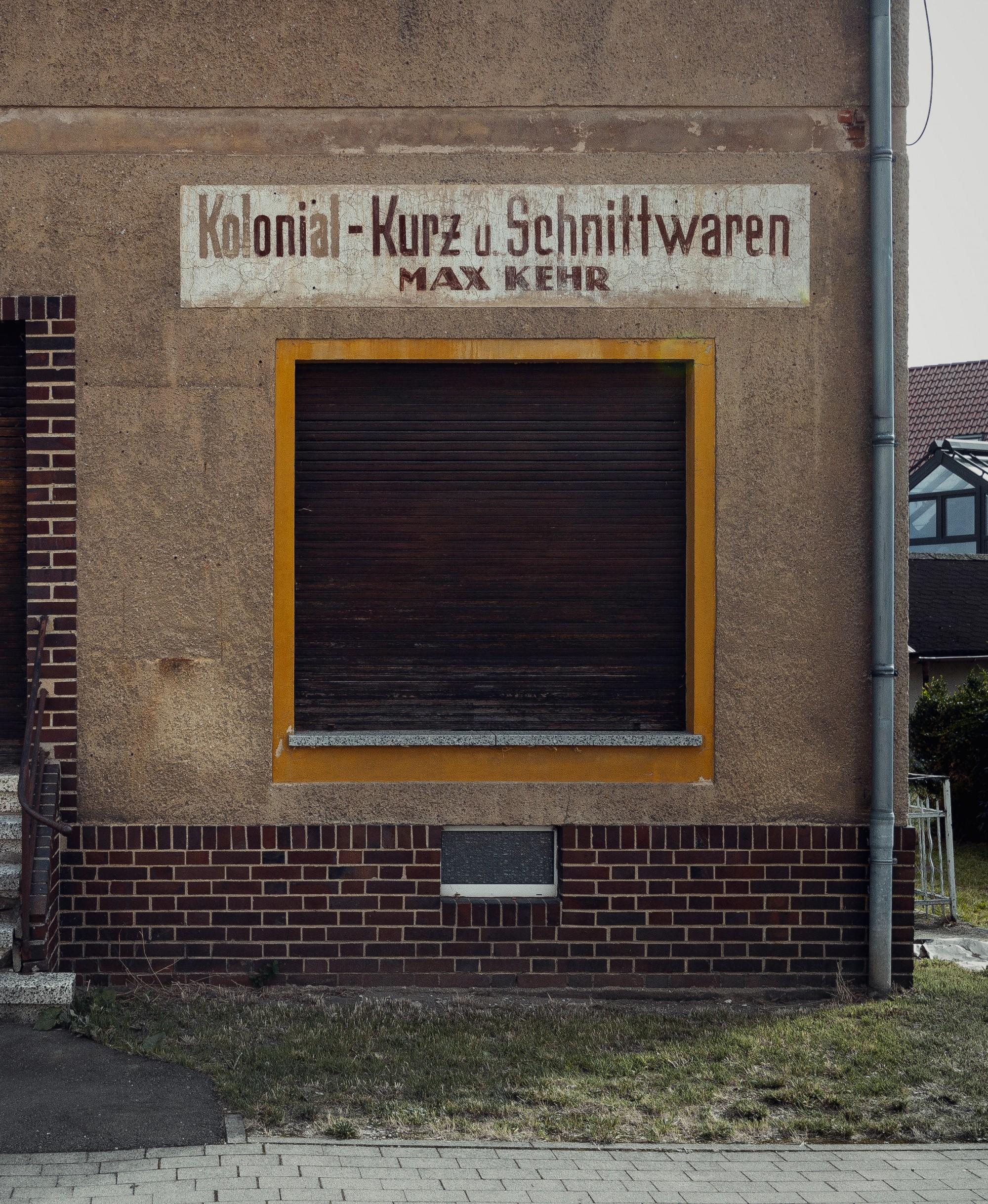 Fassade eines alten Schnittwarenladens mit gelbem Fensterrahmen