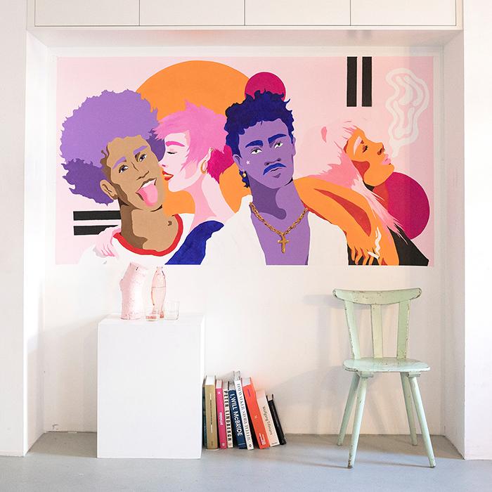 Bunte Wandmalerei mit mehreren Personen im illustrativen Stil auf einer weißen Wand, weiße Wohnaccessoires im Vordergrund