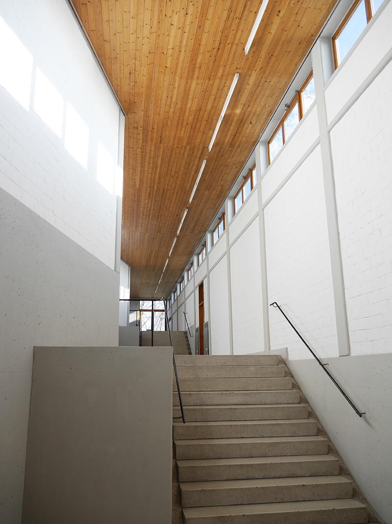 Flur mit Dachschrägen, Treppen, hölzerner Decke und Fenstern