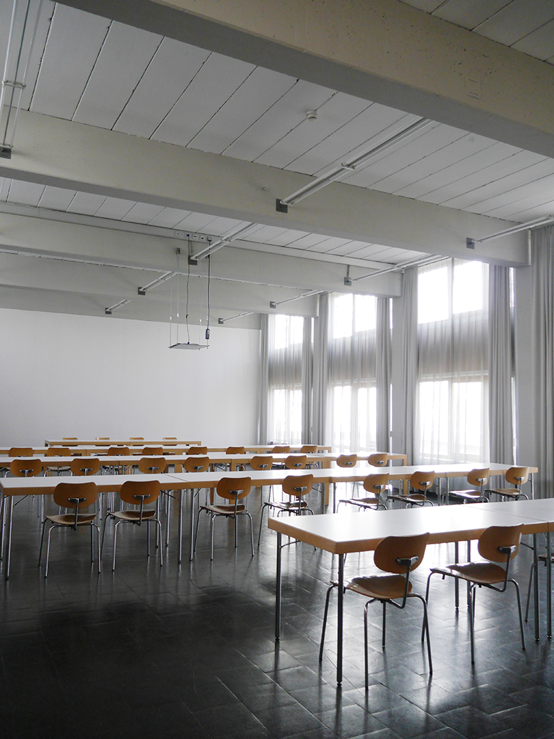 lichtdurchflutetes Klassenzimmer mit Stulhreihen, Fensterfront und Gardinen