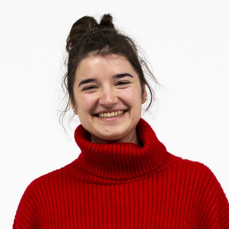 Portrait einer lachenden Studentin mit dunkelbraunen Haaren im Dutt vor weißem Hintergrund