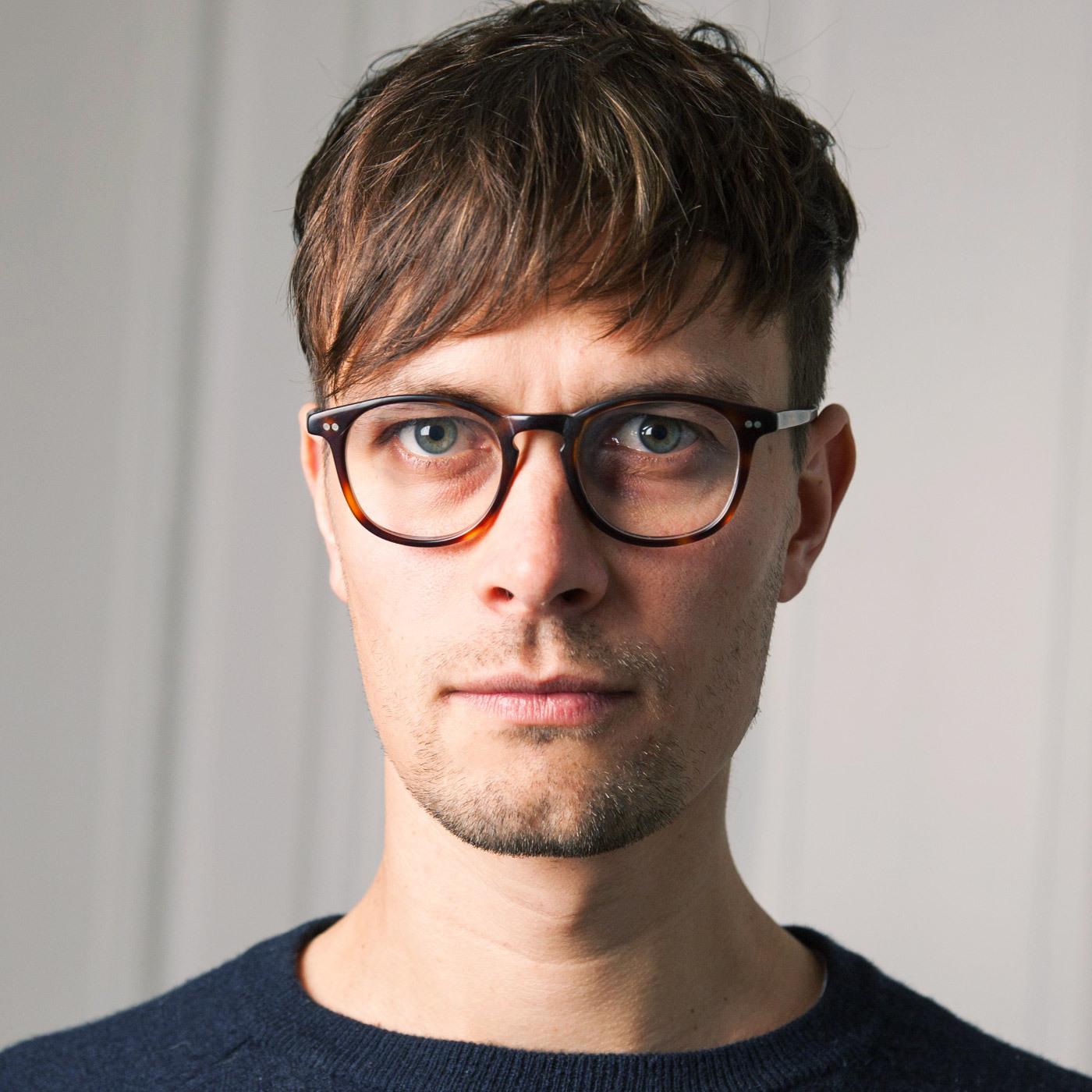 braunhaarige Mann mit brauner Brille und seriösem Gesichtsausdruck