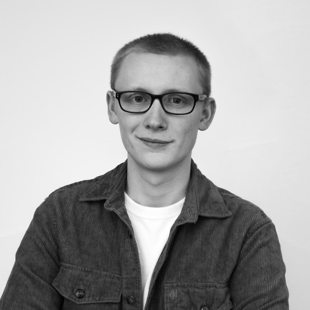 Portrait eines jungen Mannes mit Brille und kurzen dunkelblonden Haaren