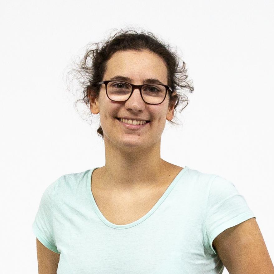 Portrait einer lachenden Studentin mit dunkelbraunen Haaren im Zopf und Brille vor weißem Hintergrund