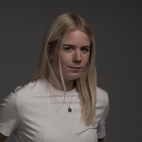 Portrait einer Studentin mit glatten blonden Haaren und skeptischem Blick vor grauem Hintergrund