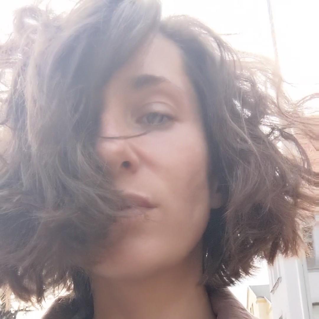 Frau mit braunem Pagenkopf, welcher das halbe Gesicht verdeckt