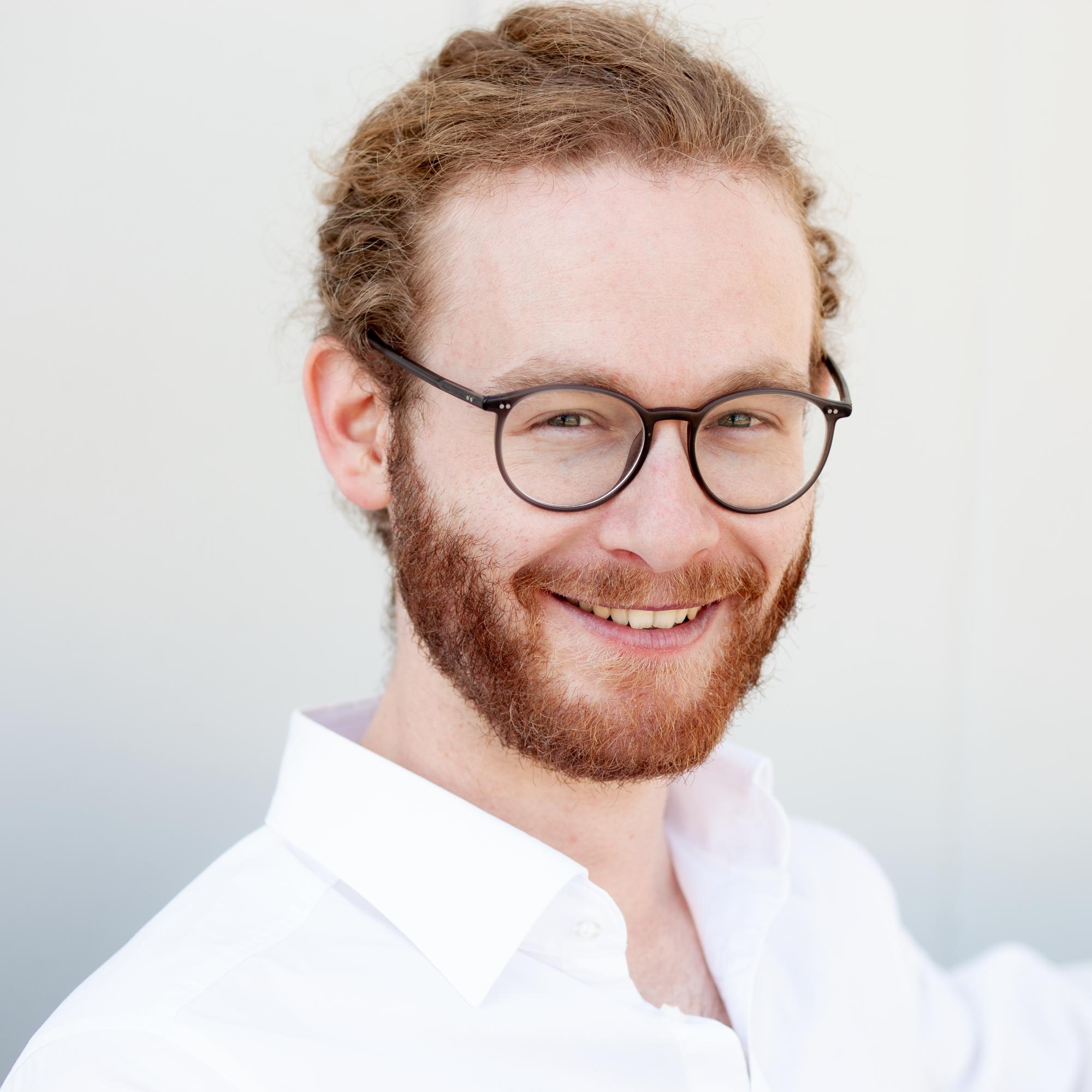 Portraitbild von jungem Mann mit langen Haaren und Brille vor weißem Grund