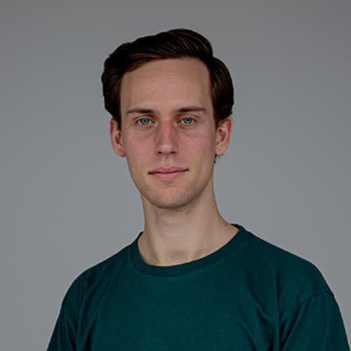 Portrait eines Studenten mit kurzen braunen Haaren und neutralem Blick vor grauem Hintergrund