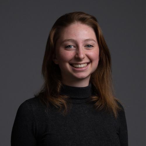Portrait einer lachenden Studenten mit mittellangen, rötlichen Haaren vor schwarzem Hintergrund