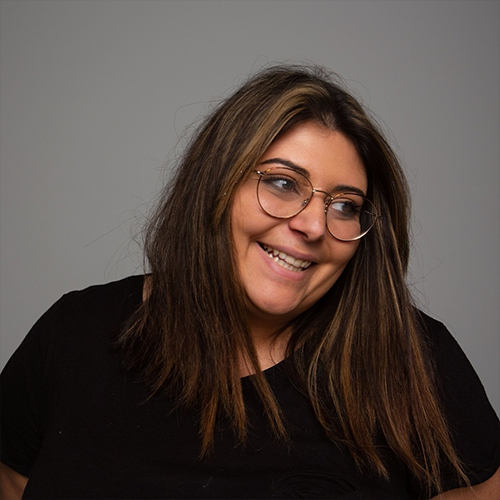 Portrait einer lachenden Studentin mit mittellangen, braunen Haaren und Brille, die rechts aus dem Bild sieht