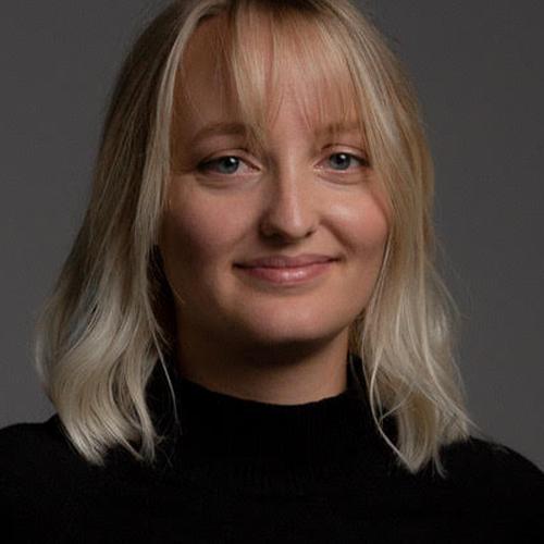 Portrait einer Studentin mit schulterlangen blonden Haaren und Ponny vor grauem Hintergrund