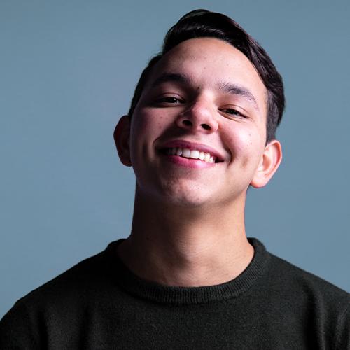 Portrait eines lachenden jungen Mannes mit kurzen schwarzen Haaren vor blauem Hintergrund