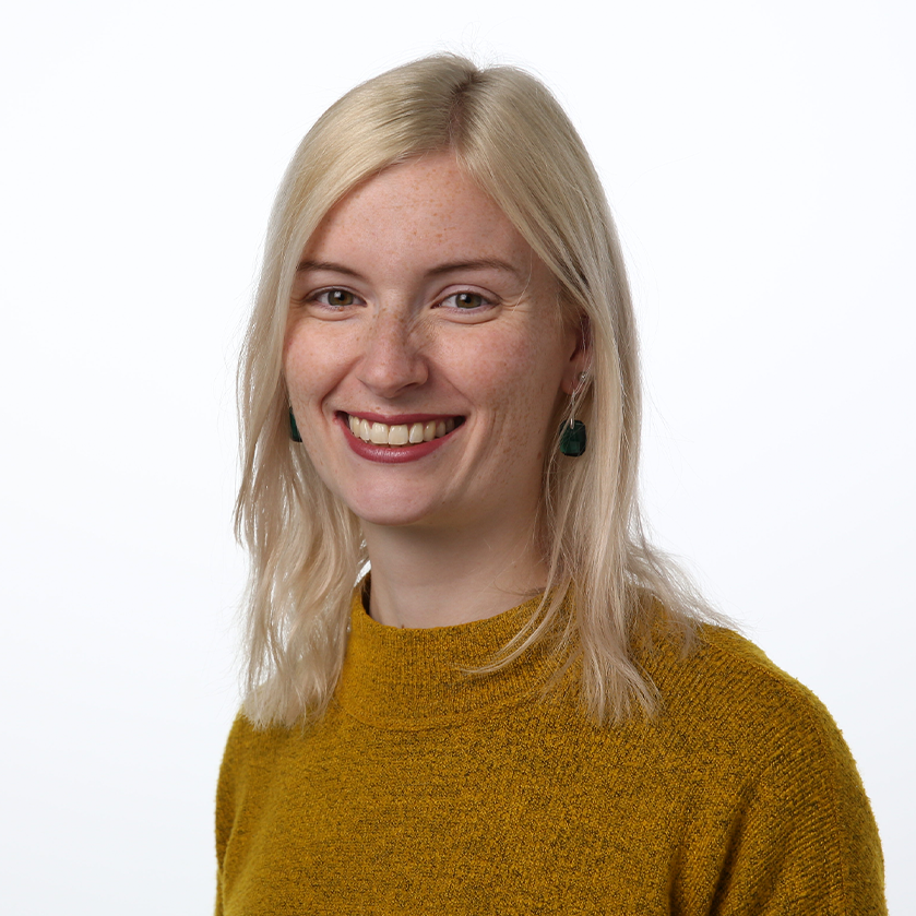 Portrait einer lachenden blonden Studentin mit roten Lippen vor weißem Hintergrund